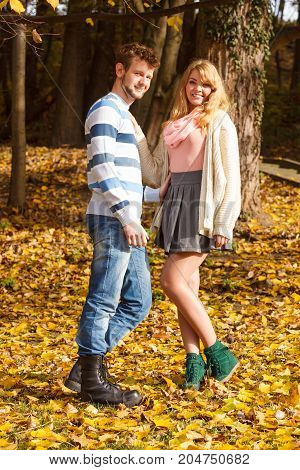 Season happiness and people concept. Relationships and feelings. Young Couple relaxing in autumnal park enjoy romantic date on sunny day.