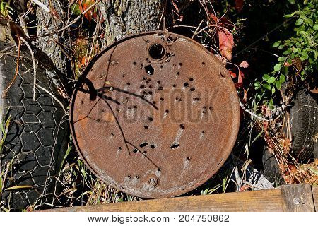 An old rusty lid of a metal barrel is perforated with bullet holes from target shooting