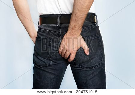 Man has Diarrhea Holding his Butt. Guy to hold with a hand a sore ass. the hand scratching a causal place.