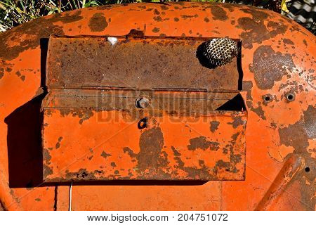 A lone wasp nest hangs from the lid of an old tool box mounted on an orange tractor fender.