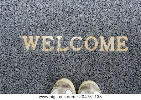 Welcome carpet with foot-ware on it.welcome cleaning foot carpet with shoes and shoe print on it.