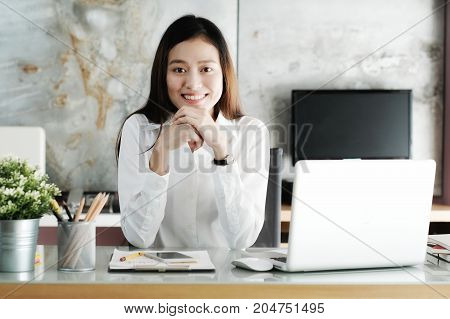 Young asian businesswoman working with with smiling face at office desk positive emotion office life concept