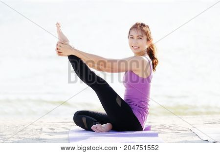 Young woman practicing yoga on beach in stretching pose wellness well being
