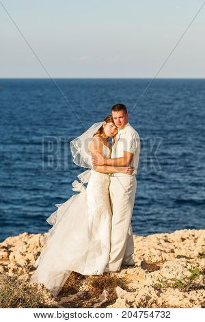 Bride and groom on a romantic moment on nature. Stylish wedding couple outdoors.