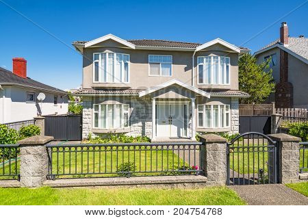 Big residential house with iron fence in front