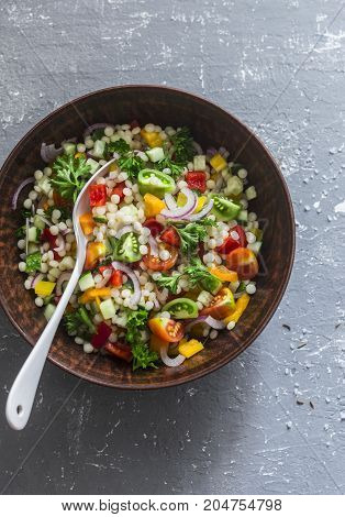 Israeli cous cous ptitim vegetables tabbouleh salad on a gray background top view. Vegetarian food concept