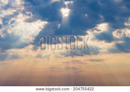 rays of the sun make their way through dramatic clouds