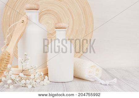 Soft elegant bathroom decor of white cosmetics bottles with comb flowers on white wood board mock up copy space.