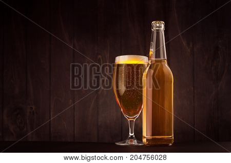 Transparent beer bottle and glass tulip with golden lager on dark brown wood board copy space mock up. Template for advertising design branding identity.