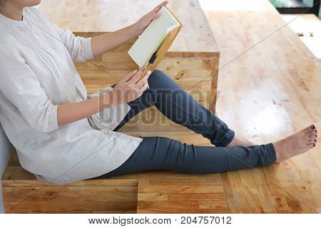 Thoughtful female student sitting Serious reading a book in a library floor Education concept