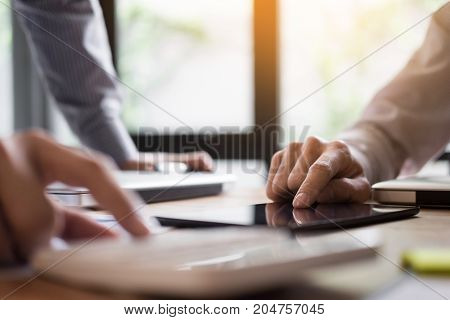 Two young businessmen using touchpad explaining his business plans to his colleagues organization meeting concept.