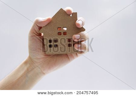Hand holding model house Mortgage loan property for concept with copy space.