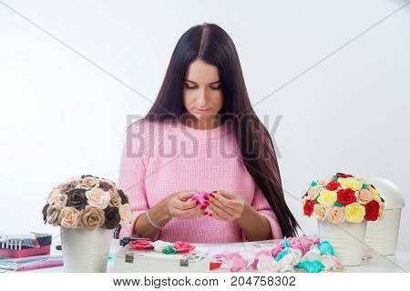 Dark-haired young woman with red nails glues roses of pink color of their foam for a bouquet of artificial flowers in a white pot on a white table are pots of flowers boxes glue