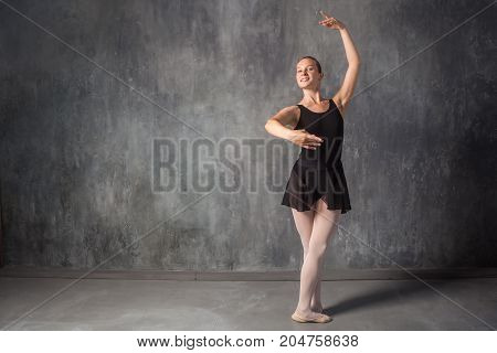 beautiful young blonde ballet dancer in a black dress white pantyhose and bouillant pointes dancing Russian ballet in a dark dance studio