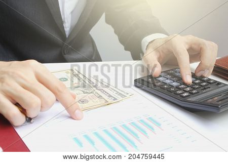 Hand use calculator on the office desk investment and property for concept.