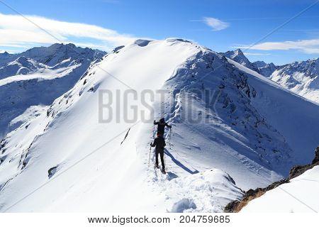 Two Men Snowshoe Hiking On Mountain Snow Arete And Panorama In Stubai Alps, Austria