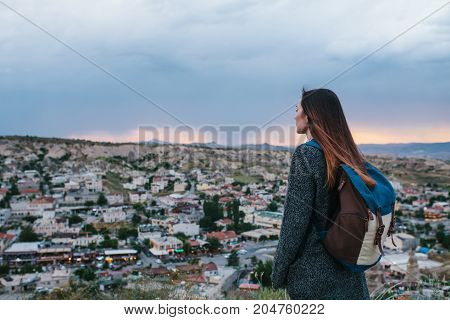Young woman tourist from a high point looking at the sunset over the city of Goreme in Turkey and dreaming. Tourism, vacation.