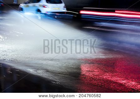 Blurred View Of Water Splashes From Car Wheels During Rainy Weather