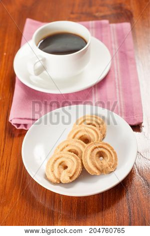 Round shaped cookie and coffee on table.