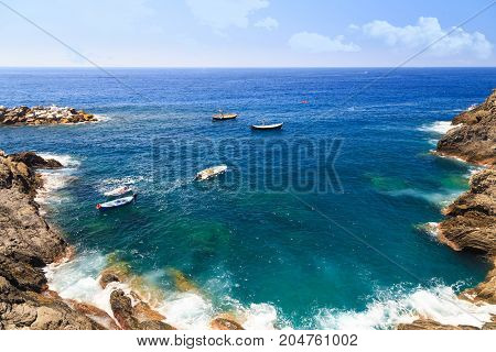 Mediterranean seascape - blue sea framed by rocks on bright summer day. Waves break against the rocks. Boats in the lagoon. Top view. Manarola Italy Cinque Terre National Park Ligurian Riviera