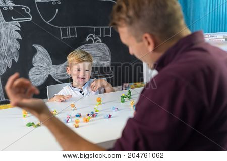 Cute little playfull toddler boy at child therapy session. Private one on one homeschooling with didactic aids.