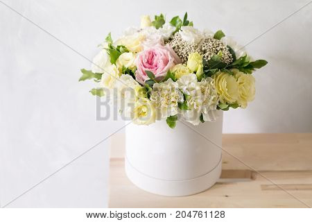 Beautiful tender bouquet of flowers in white box on light ackground with space for text . assembled a bouquet of professional florists. gentle colors