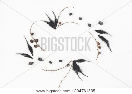Frame made of black bird feathers larch branches pine cones. Flat lay top view copy space