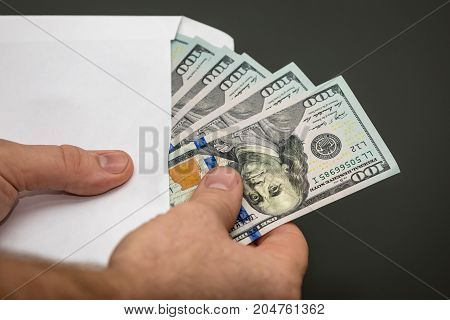 A person counting money in  an envelope