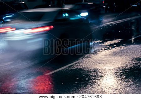 Cars Driving On Wet Road At Rainy Night