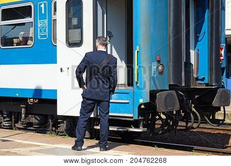 Train conductor next to a railway carriage