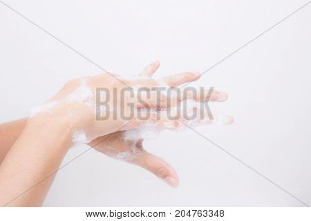 Asian girl's hands are washing with soap bubbles on white background