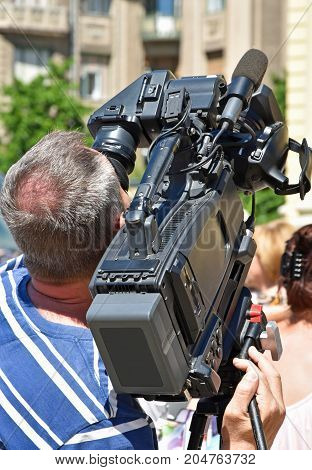 Cameraman at work outdoor in summer time