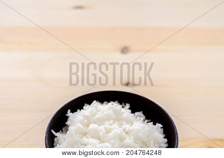 Rice In The Black Bowl On Wood Table Background