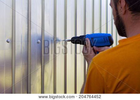 a bearded man with a screwdriver in hand screwed the screws sheets metal profile selective focus