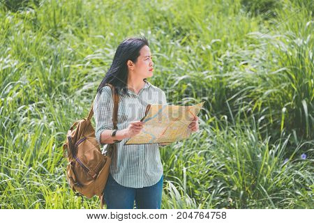 Asian traveler with backpack open map and looking forward to see direction on road near green grass in sunny dayAlone travel or single traveler concept.