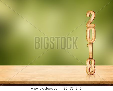 2018 new year number ( 3d rendering ) on brown wood table top with blur green nature bokeh background Template mock up for display or montage of product in holiday seasonal