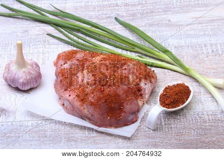 pork steaks with fat. Meat is on wooden board with spice as pepper and green spring onion. Ready for cooking. Selective focus