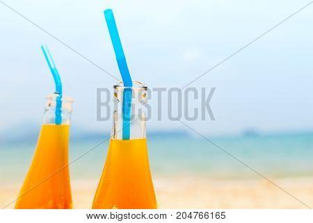 Two Orange Juice Bottles Sea Background Summer