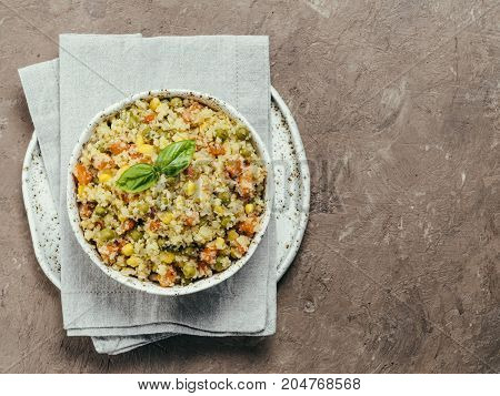 Top view of cauliflower rice with vegetables. Organic paleo Cauliflower Rice with corn, green peas and carrots on brown concrete background. Copy space.