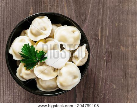 Close up viw of traditional russian pelmeni, ravioli, dumplings with meat on brown wooden background. Copyspace. Top view or flat lay. Russian food and russian kitchen concept.