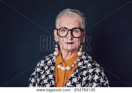 Stylish and elegant elderly woman in glasses on a black background.