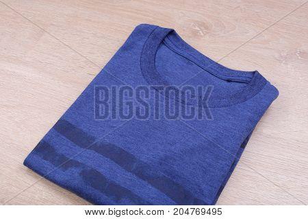Folded blue stripe tshirt on wooden background