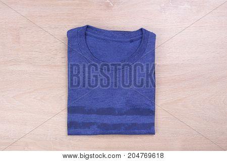 Blue stripe folded tshirt on wooden background