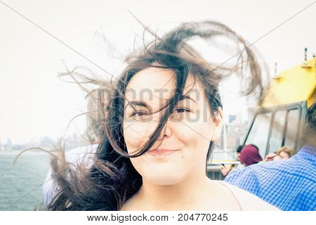 Close up of a Young Woman on board a New York Ferry Trip with wind creating her hair to whirl.