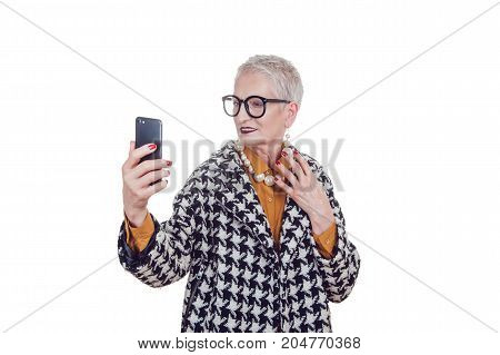 Stylish old woman in glassesmakes selfie isoladed on white.