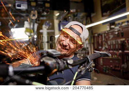 Cute photo. Mechanic repairing a mountain bike in a workshop
