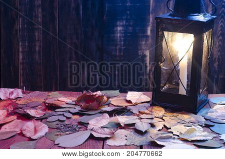 a lamp with a burning candle on a wooden background with leaves