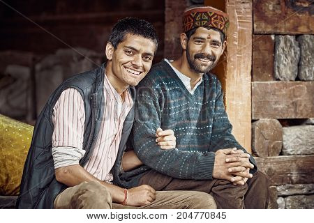 Naggar India - August 2017. Two traditional Indian mens sit near the house look and smile at the camera. Naggar Himachal Pradesh. North India.