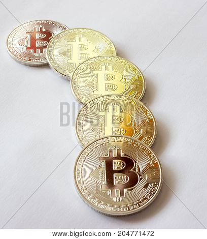 On a grey background are silver coins of a digital crypto currency Bitecoin.