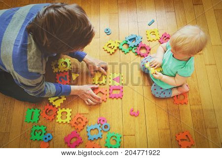 teacher and little baby playing with number puzzle, kids learning